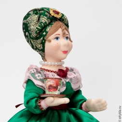 Doll warmer on a teapot with a cup of tea in a green dress